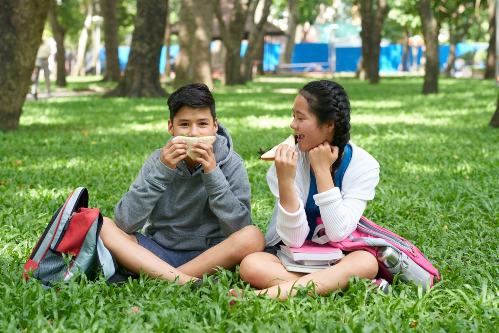 Happy school kids sitting on grass in park eating sandwiches for lunch