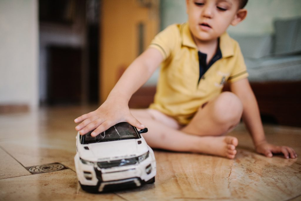 kid-playing-with-his-model-car-sitting-on-the-floo-RJ6Y38K